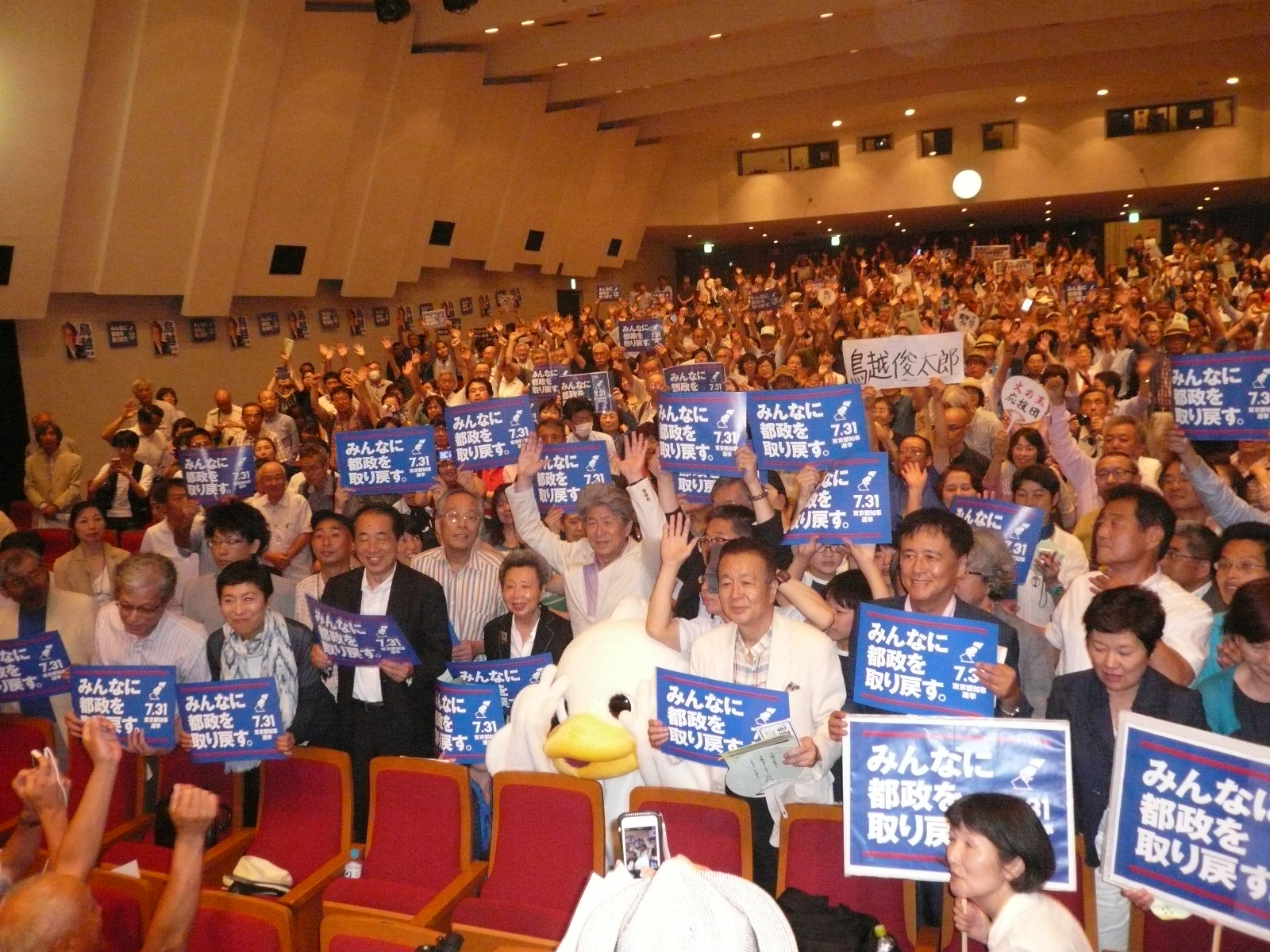 ▲鳥越俊太郎を応援する市民センター発足集会・演説会には、鳥越さんを推薦、応援する4政党と、東京・生活者ネットワークを始めとする3つの政治団体の代表が檀上に並び、応援のメッセージを述べた。応援に集まった聴衆と勝利を誓い合う鳥越俊太郎候補。7月18日、神保町の日本教育会館ホール